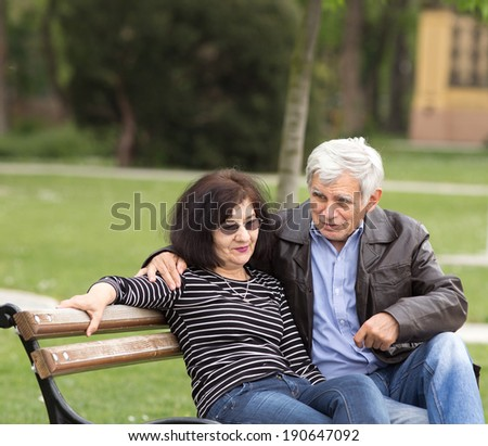 Older couple in hug sitting on bench in park - stock photo