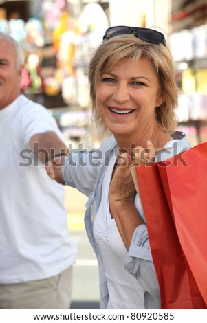Older couple larking about on holiday - stock photo