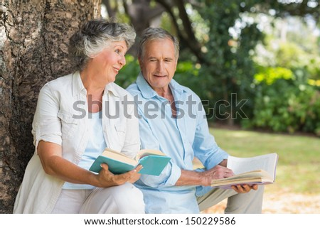 Older couple reading books together sitting on tree trunk at the park on sunny day - stock photo