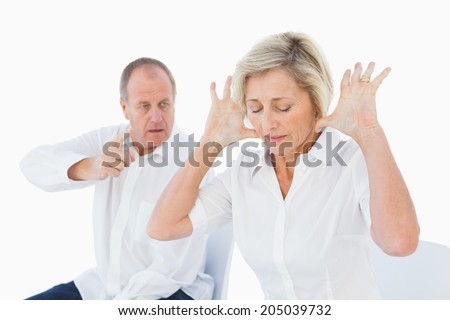 Older couple sitting in chairs arguing on white background - stock photo