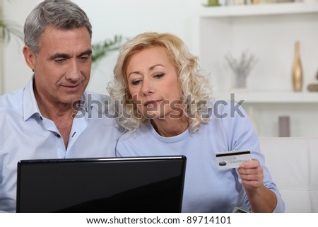 Older couple using a credit card online - stock photo