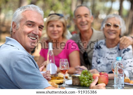 Older couples enjoying an alfresco lunch - stock photo