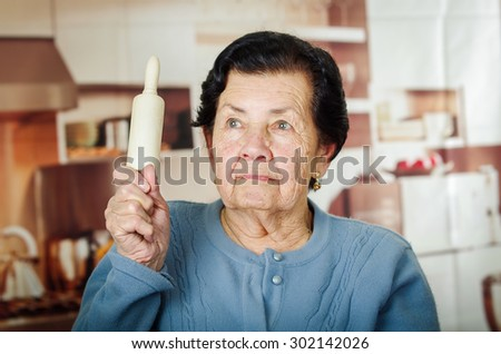 Older cute hispanic woman in blue sweater holding up a rolling pin. - stock photo