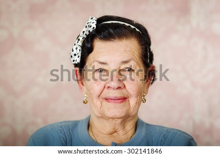 Older cute hispanic woman wearing blue sweater and polka dot bowtie on head smiling carefully in front of pink wallpaper. - stock photo