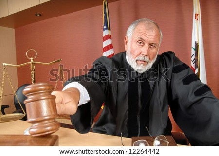 Older, distinguished judge making his ruling in the courtroom - stock photo