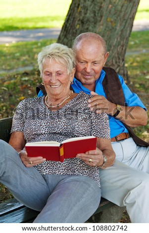 older elderly couple in love. man gives a rose. - stock photo
