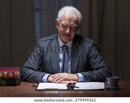 Older elegant businessman sitting in office with paperwork - stock photo
