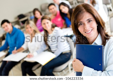 Older female student in class holding a notebook - stock photo