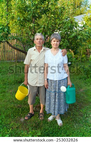 older gardeners with a pail and watering can - stock photo
