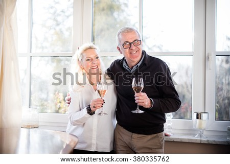 Older good looking and handsome couple drinking champagne at home and clinking glasses - stock photo