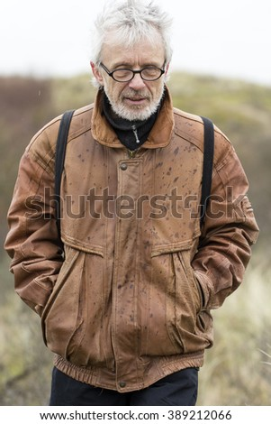 Older Grey Haired Man in the Dunes on a Rainy Cloudy Day - stock photo