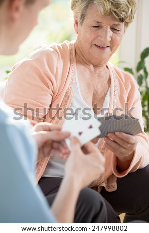 Older happy woman playing cards with her male nurse - stock photo