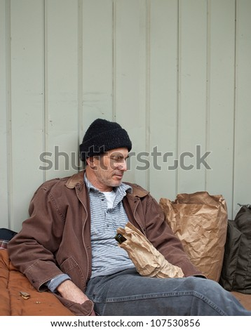 Older homeless man sleeping in a seated posture, leaning on a metal wall, surrounded by his pack, sleeping bag, wine bottle in a paper bag, etc.
