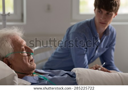 Older ill man with nasal cannula sleeping in hospital bed - stock photo