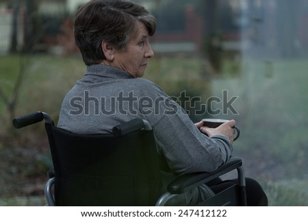 Older injured depressed woman relaxing with cup of tea - stock photo