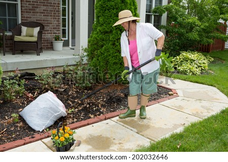 Older lady doing cleaning work in the yard preparing a flowerbed near the house for planting seedlings bought at the local nursery - stock photo
