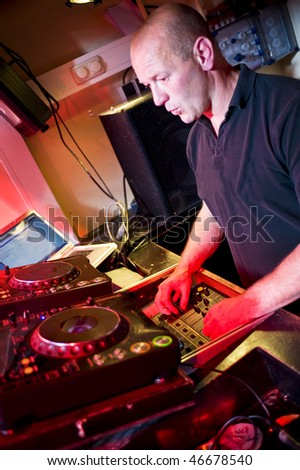 Older male as Disk jockey behind the mixing panel - stock photo