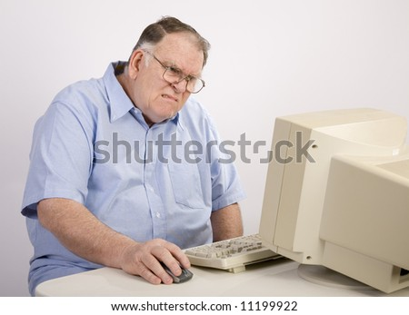 older male working on computer and grimacing - stock photo