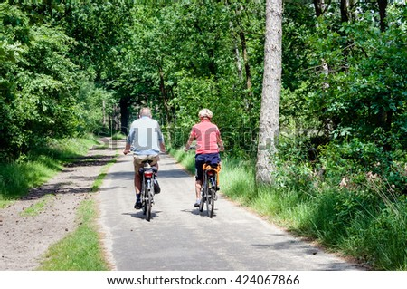 Older man and woman cycling together along a bike path through the forest. It's a warm day in summer.