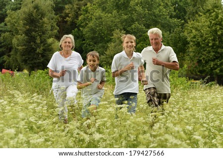 Older man and woman running with their grandchildren outdoors - stock photo