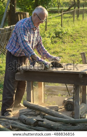 Older man cutting woods with circular saw