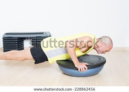 Older man making suspension training - stock photo