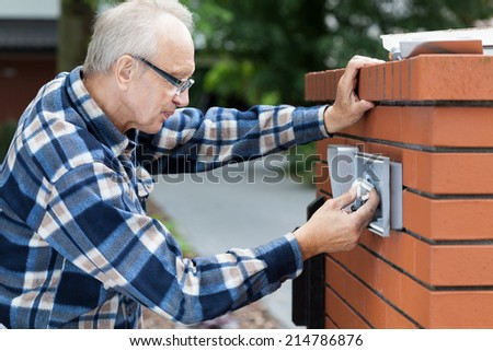 Older man repairing intercom at the gate - stock photo