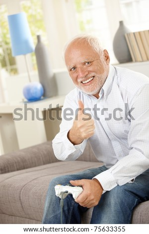 Older man sitting on couch giving thumb up while playing computer game, looking at camera, smiling.? - stock photo