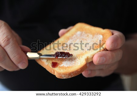 Older man spreads grape jam on a slice of buttered toast, copy space included.