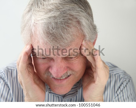 older man suffers from a very bad headache - stock photo