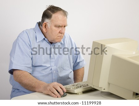 older man surfing the net and not happy - stock photo