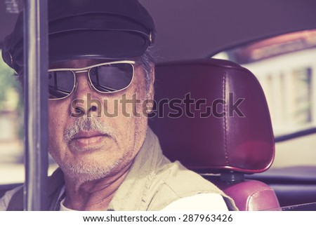 Older man with glasses driving a car - stock photo