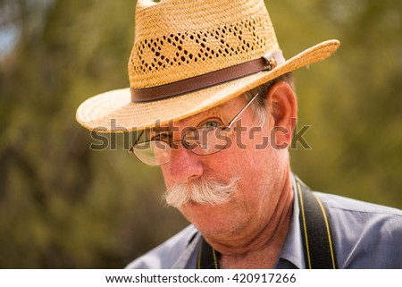 Older man with hat, making a goofy face - stock photo