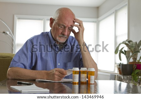 Older man with prescription medications. - stock photo