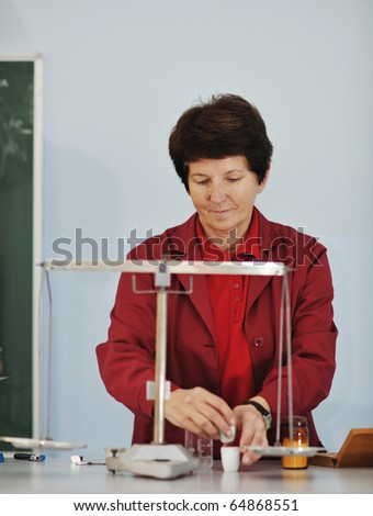 older or senior science and chemistry teacher woman portrait at classroom school indoor - stock photo