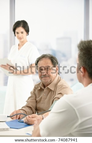 Older patient at consultation with doctor, nurse standing in background. - stock photo