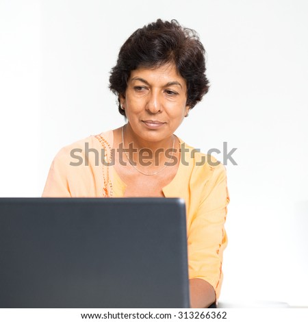 Older people and modern technology concept. Portrait of a 50s Indian mature woman using laptop computer at home. Indoor senior people living lifestyle. - stock photo