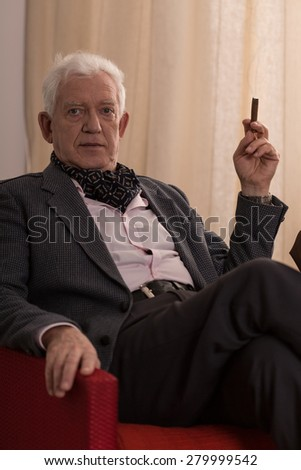 Older retired businessman sitting alone with ciagr in his chair - stock photo