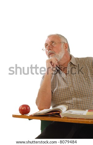Older scholar sitting at a desk with a book; isolated on white
