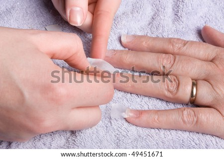 Older senior woman's hand receiving home spa/beauty treatment of nail extensions.