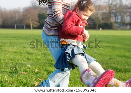 Older sister carrying younger sister and turning around joyfully playing games while in a green park during a sunny winter day, having fun outdoors. - stock photo