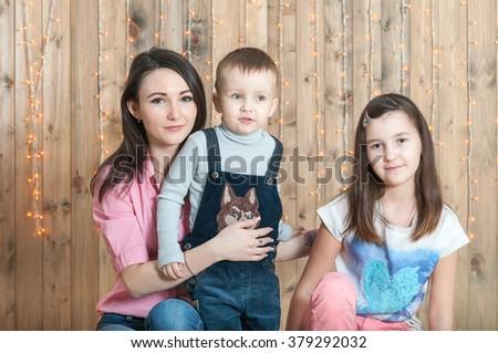 Older sister hold hands with her young sister and hug their little brother near wood wall with garland - stock photo