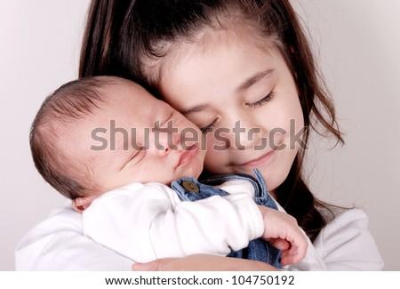 older sister hugging newborn baby brother - stock photo