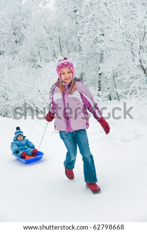 Older sister rolls her brother on a sled in winter park - stock photo