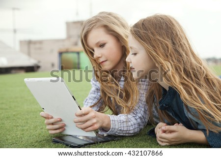 older sister shows something in his tablet PC Junior, lying on the green lawn