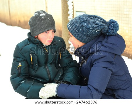older sister soothing younger crying brother on snow winter background - stock photo