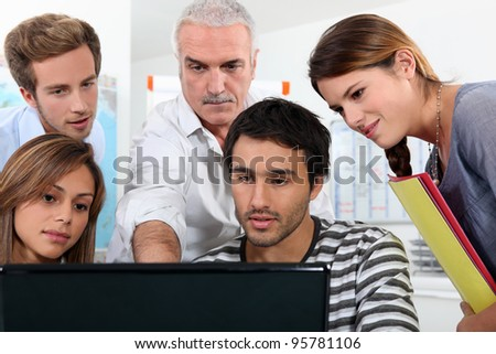 Older students and teacher gathered round a computer - stock photo