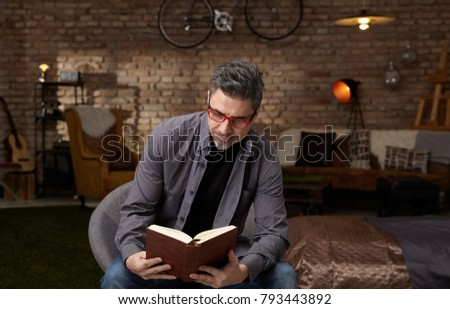 Older white man reading book at home. Wearing casual, gray hair and trendy red glasses.
