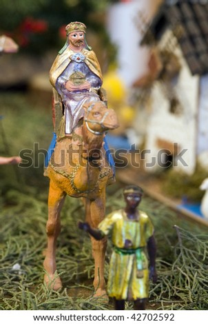 Older wise king with dromedary and page. Focus in wise king figurine. - stock photo