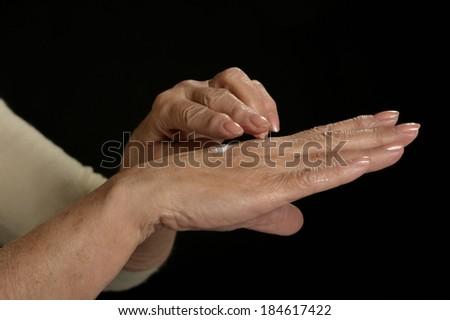 Older woman applying cream on hands closeup on black background - stock photo